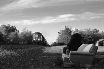 a woman sits facing away from the camera on a sofa at the edge of the train tracks as a train approaches. Black and white still from the film Oklahoma Mon Amour (dir. Carolina Rueda)