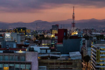 Photo taken from a Centro Historico rooftop, Mexico City in the evening. There are hills in the distance, and dense buildings in the foreground with lights and signs.